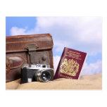 Una maleta de cuero vieja, una cámara retra y tarjeta postal
