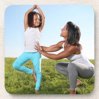 Una mamá ayuda a su chica de cinco años con una yo posavasos