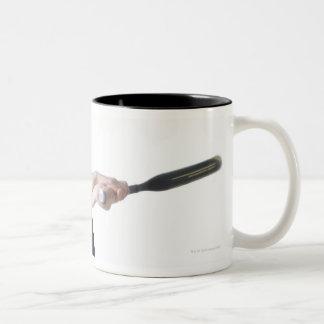 una mujer caucásica joven bonita está llevando a taza de dos tonos