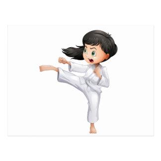 Una mujer joven que hace karate postal
