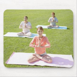 Una mujer joven que hace yoga alfombrilla de ratones