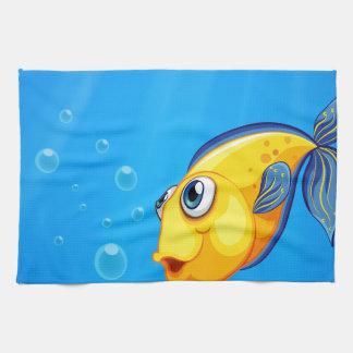 Una natación amarilla de los pescados debajo del toalla de mano