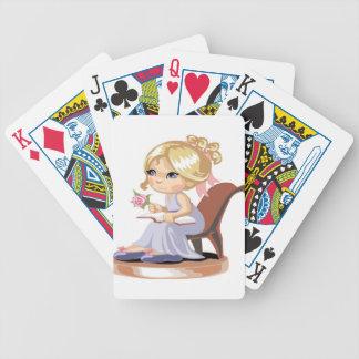 Una niña en un camisón azul barajas de cartas