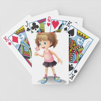 Una niña linda que sostiene un lollipop barajas de cartas