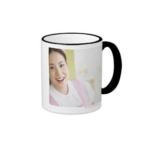 Una niñera sonriente tazas