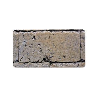 Una pared de piedra vieja con las grietas etiqueta de dirección