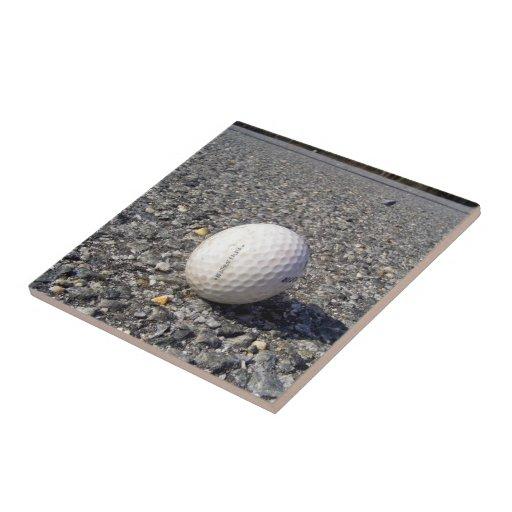 Una pelota de golf que descansa sobre la grava tejas  ceramicas