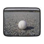 Una pelota de golf que descansa sobre la grava funda macbook air
