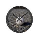 Una pelota de golf que descansa sobre la grava reloj de pared