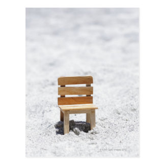 Una pequeña silla en la playa arenosa postales