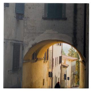 Una persona que camina debajo de un arco, abajo de azulejo cuadrado grande