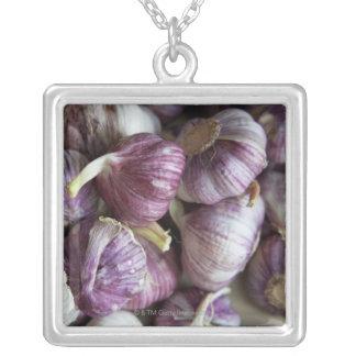 una pila de ajo fresco exhibida para la venta collar plateado