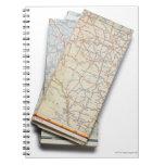 Una pila de mapas de camino doblados en un blanco cuaderno