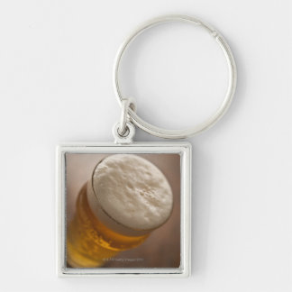 Una pinta de cerveza dorada, foco bajo del lir llavero cuadrado plateado