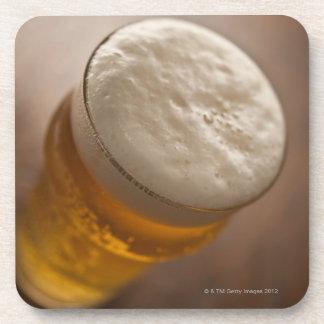Una pinta de cerveza dorada, foco bajo del lir tra posavasos