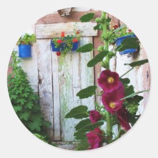 Una puerta azul vieja rústica hermosa en un jardín pegatina redonda