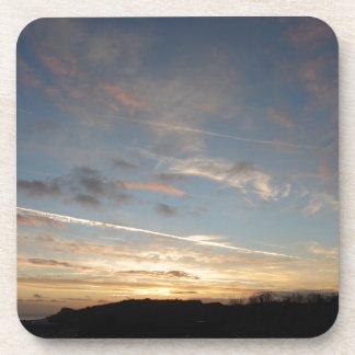 Una puesta del sol hermosa en el horizonte en posavasos de bebida