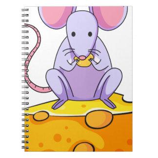 Una rata que come sobre la rebanada grande de libro de apuntes con espiral