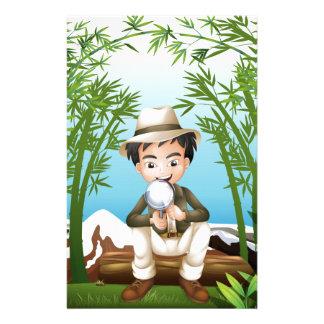Una selva tropical con un hombre que sostiene una  papeleria