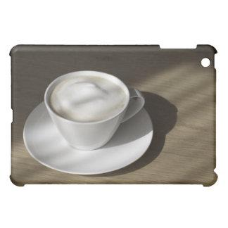 Una taza de café del cappuccino miente en un roble
