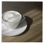 Una taza de café del cappuccino miente en un roble teja  ceramica