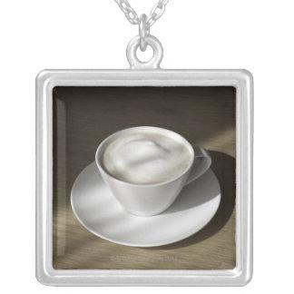 Una taza de café del cappuccino miente en un roble collar plateado