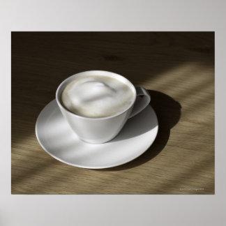 Una taza de café del cappuccino miente en un roble póster