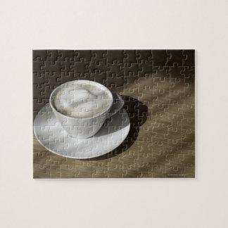 Una taza de café del cappuccino miente en un roble rompecabeza