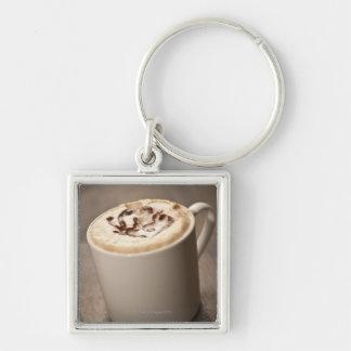 Una taza de café del Cappuccino remató con Llavero Cuadrado Plateado