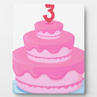 Una torta con la vela placas con fotos