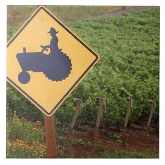 Una travesía amarilla del tractor firma adentro el azulejo cuadrado grande