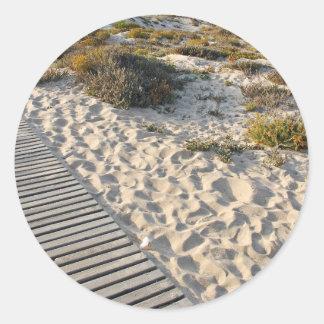 Una trayectoria de madera que lleva a una playa pegatina redonda