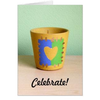 Una vela votiva en un pote de arcilla del corazón felicitacion