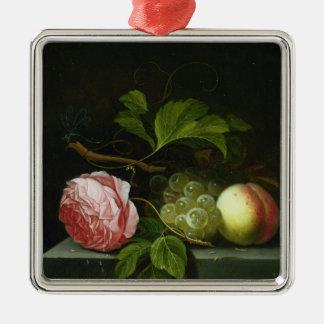 Una vida inmóvil con un color de rosa, las uvas y adorno cuadrado plateado