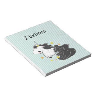 Unicornio negro del dibujo animado con la libreta blocs