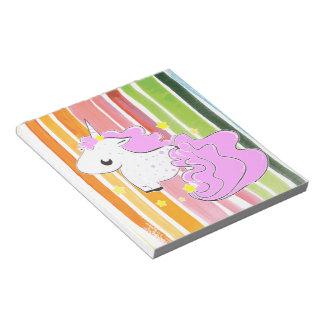 Unicornio rosado del dibujo animado con la libreta blocs