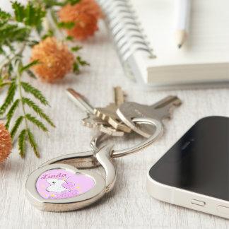 Unicornio rosado lindo del dibujo animado con las llavero plateado en forma de corazón