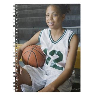 Uniforme del baloncesto del adolescente que lleva libreta