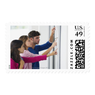University students checking bulletin board for postage