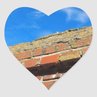 Upper part of the stone wall of bricks against a b heart sticker