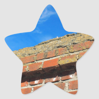 Upper part of the stone wall of bricks against a b star sticker