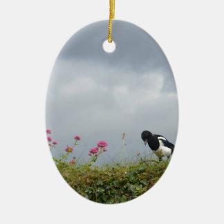 Urraca y flores salvajes adorno navideño ovalado de cerámica