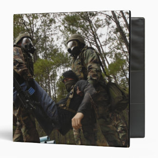 US Air Force Airmen carry a simulated casualty 3 Ring Binder