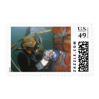 US Navy Diver uses a grinder Stamp