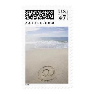 USA, Massachusetts, At sign drawn on sandy beach Postage