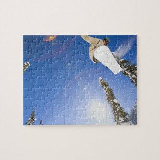 USA, Montana, Whitefish, Young man snowboarding Puzzle