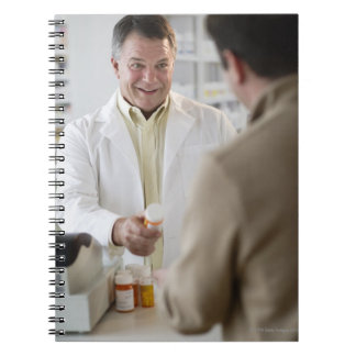 USA, New Jersey, Jersey City, Pharmacist selling Notebook
