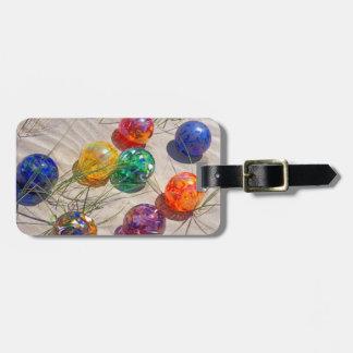 USA, Oregon. Colorful Glass Floats On Sand Dune Bag Tag