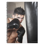 USA, Seattle, Portrait of young man boxing in Note Book