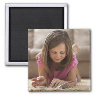 USA, Utah, Lehi, Girl (10-11) lying on rug, Magnet